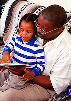 African American father reads to his young son.