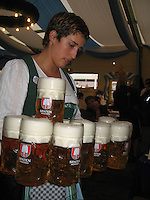 A woman carries heavy steins of beer at Oktoberfest - Munich, Germany
