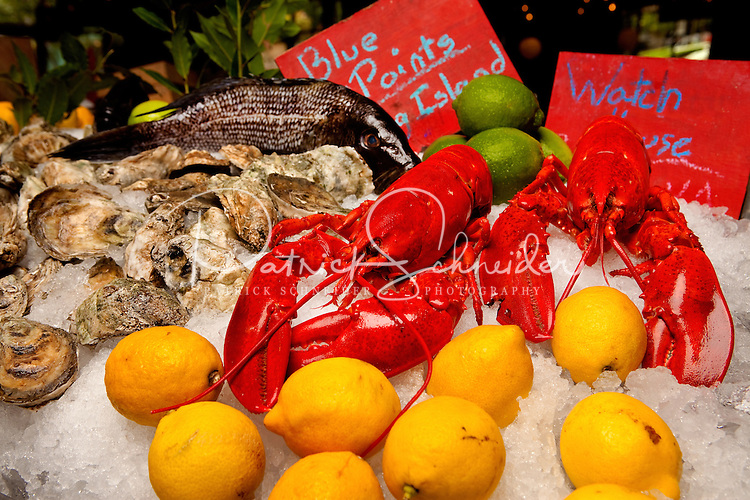 Detail photo of lobster, lemon and oysters over ice