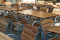 Empty restaurant tables and chairs in a courtyard, Bordeaux, France.