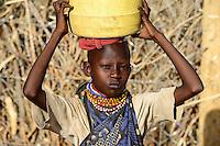 KENYA Turkana, Lodwar, Turkana village Kaitese, Turkana girl carry water from well / KENIA Turkana, Lodwar, Turkana Dorf Kaitese, Turkana Maedchen holt Wasser vom Brunnen