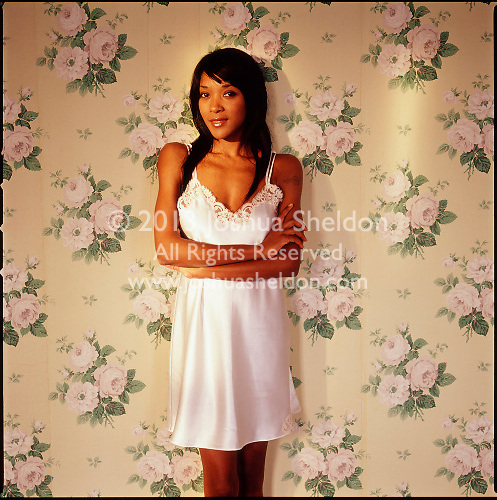 African American woman wearing negligee leaning against floral wallpapered wall