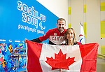 Sochi, RUSSIA - Mar 5 2014 -  Benoit Huot, closing ceremonies flag bearer for the London 2012 Paralympic Summer Games passes the flag to Wheelchair Curling's Sonja Gaudet after she was names as Canada's opening ceremonies flag bearer prior to the Sochi 2014 Paralympic Winter Games in Sochi, Russia.  (Photo: Matthew Murnaghan/Canadian Paralympic Committee)
