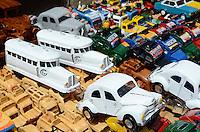 MADAGASCAR, city Antananarivo, street vendor sells small toy cars Citroën 2CV and miniature of vintage railcar La Micheline with tube tyres recycled from used beverage cans / MADAGASKAR Hauptstadt Antananarivo, Strassenverkaeufer verkauft Spielzeug Autos der Citroën 2CV Ente und den Miniatur Triebwagen mit luftbereiften Gummireifen La Micheline aus Blech von recycelten Getraenkedosen