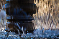 A flowing water fountain creates one of a series of abstract images in an urban city center.
