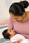 newborn baby girl one month old  Mexican American with mother held interation vertical