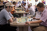Men playing chess in Harvard Square on stone tables in plaza across from Harvard University, Cambridge, M