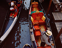 View from a bridge over a Venice canal into a very regal-looking gondola.