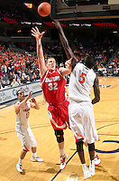 Dec. 07, 2010; Charlottesville, VA, USA;  Radford Highlanders center Martins Abele (32) shoots between Virginia Cavaliers guard Sammy Zeglinski (13) and Virginia Cavaliers center Assane Sene (5) during the game at the John Paul Jones Arena. Virginia won 54-44. Mandatory Credit: Andrew Shurtleff