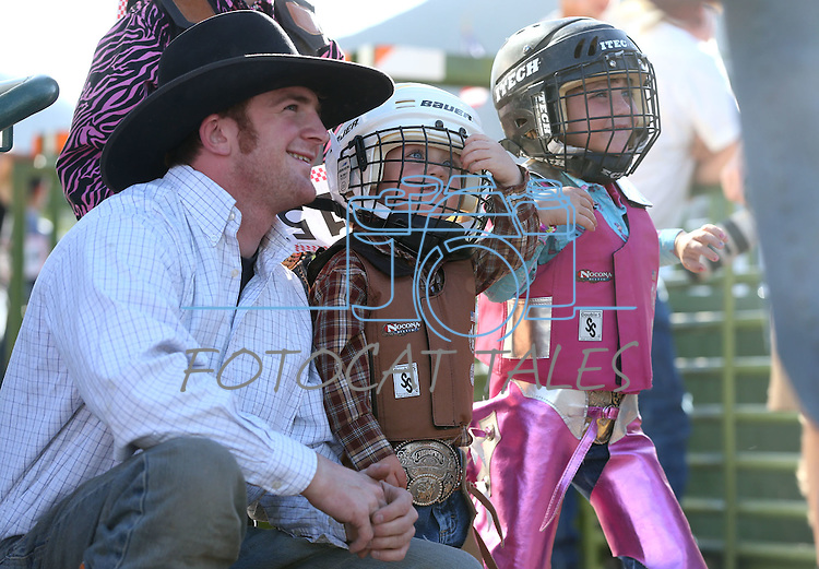 Weston Starr, 2, and his sister Payslee, 4, of Fallon, wait for the start of the mutton bustin' event with their uncle Blaine Tibbals at the Smackdown Tour at Fuji Park in Carson City, Nev., on Saturday, June 7, 2014.<br /> Photo by Cathleen Allison