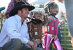 Weston Starr, 2, and his sister Payslee, 4, of Fallon, wait for the start of the mutton bustin' event with their uncle Blaine Tibbals at the Smackdown Tour at Fuji Park in Carson City, Nev., on Saturday, June 7, 2014.<br />