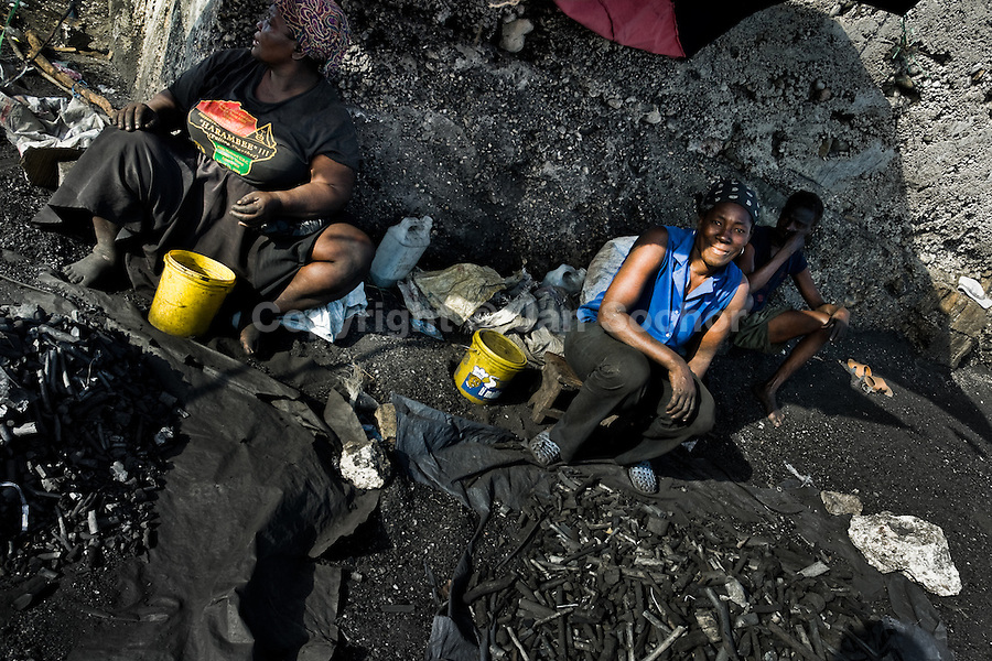 Haitian women sell charcoal in the slum of Cité Soleil, Port-au-Prince, Haiti, 21 July 2008. Cité Soleil is considered one of the worst slums in the Americas, most of its 300.000 residents live in extreme poverty. Children and single mothers predominate in the population. Social and living conditions in the slum are a human tragedy. There is no running water, no sewers and no electricity. Public services virtually do not exist - there are no stores, no hospitals or schools, no urban infrastructure. In spite of this fact, a rent must be payed even in all shacks made from rusty metal sheets. Infectious diseases are widely spread as garbage disposal does not exist in Cité Soleil. Violence is common, armed gangs operate throughout the slum.