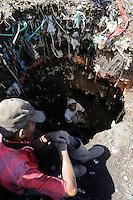 """MADAGASCAR Antananarivo, dumping site, people live from waste picking, father and son digging for metal, catholic priest Per Pedro Opeka has build Akamasoa a social community project with housing schemes, health units and schools for ragpicker / MADAGASKAR Antananarivo , Muellsammler auf einer Muellkippe, Vater und Sohn graben im Muellberg nach Metallen, Pater Pedro Opeka hat die Gemeinde Akamasoa , auf madagassisch """"gute Freunde"""" , mit Muellsammlern, Bettlern und Sozialschwachen auf einem Huegel bei Antananarivo erbaut, Teil des Projektes sind Hausbau, Schulen, Krankenhaeuser und Beschaeftigung"""