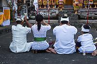 Bali, Indonesia.  Hindu Family Praying for a Bountiful Rice Harvest.  Pura Dalem Temple.  Dlod Blungbang Village.