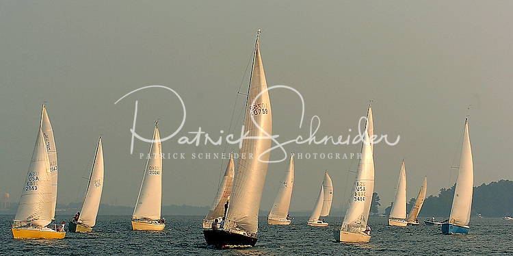 Sailboats sail in the evening light on Lake Norman in NC.