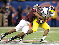 Antone Exum of Virginia Tech tackles Kevin Koger of Michigan during Sugar Bowl game at Mercedes-Benz SuperDome in New Orleans, Louisiana on January 3rd, 2012.  Michigan defeated Virginia Tech, 23-20 in first overtime.