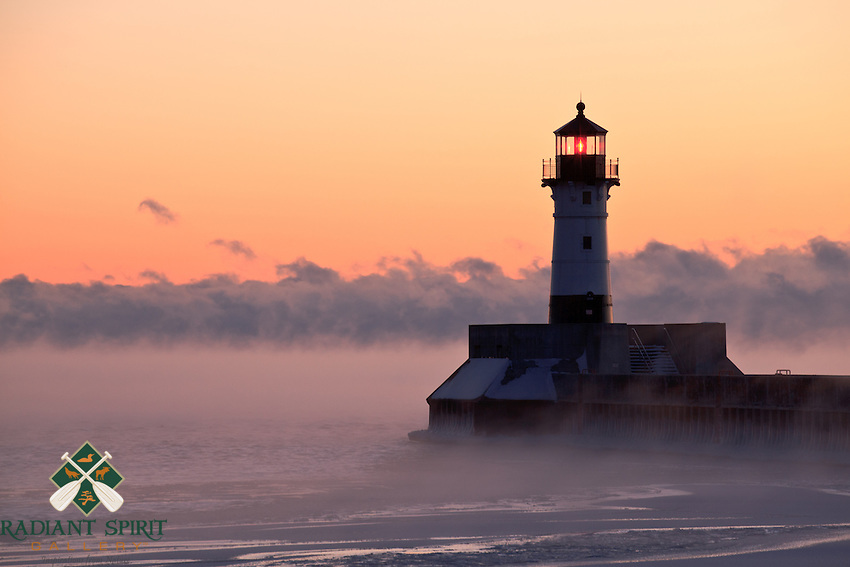 """""""Steamy Sunrise""""<br /> Canal Park's lighthouse stands among Lake Superior's steam devils during a subzero sunrise in Duluth."""
