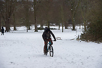 A cyclist tries to ride his bicycle through snowfall at Foots Cray Meadow, Sidcup, Kent, England on the 9 February 2021. Photo by Alan Stanford.