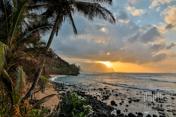 Sunset over the ocean with distant Bali Hai (or Mount Makana), seen through jungle foliage at Princeville, Kaua'i.