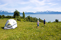 USA, Alaska, Two children, brother and sister play among the wildflowers in their campsite complete  with views of Kachemak Bay and the Kenai Peninsula at Seaside Farm Hostel in Homer.MR