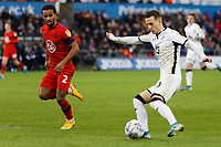 Bersant Celina of Swansea City (R) crosses the ball past Nathan Byrne of Wigan Athletic during the Sky Bet Championship match between Swansea City and Wigan Athletic at the Liberty Stadium, Swansea, Wales, UK. Saturday 18 January 2020