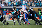 Jacksonville Jaguars Patrick Omameh (77) and Cam Robinson (74) block as Kyle Williams (95) rushes during an NFL Wild-Card football game against the Buffalo Bills, Sunday, January 7, 2018, in Jacksonville, Fla.  (Mike Janes Photography)