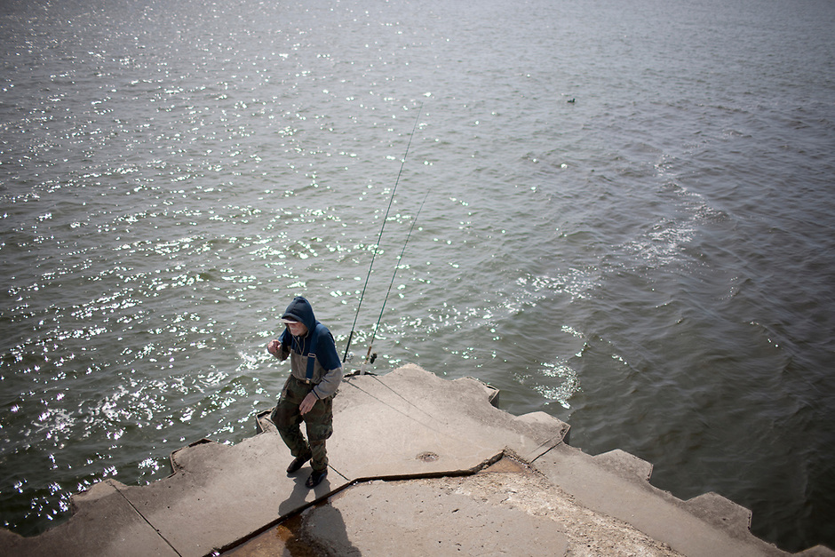 A fisherman checks his lines on Saturday, April 19, 2014, on the Silver Beach fishing pier in St. Joseph, Mich. (Photo by James Brosher)