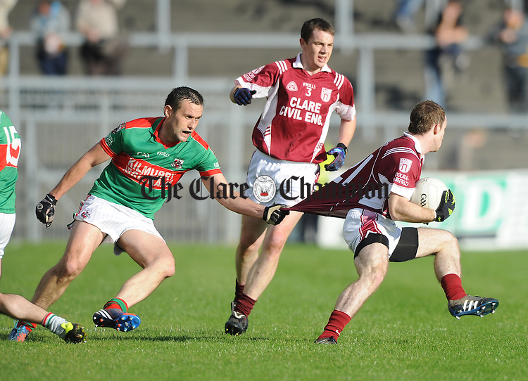 Peter O Dwyer of Kilmurry Ibrickane in action against Enda Lyons of Doora Barefield during the senior county football final at Cusack park. Photograph by John Kelly.