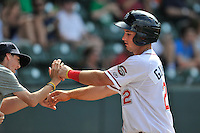 First baseman Mitchell Gunsolus (22) of the Greenville Drive is congratulated after scoring a run a game against the Lakewood BlueClaws on Sunday, June 26, 2016, at Fluor Field at the West End in Greenville, South Carolina. Greenville won, 2-1. (Tom Priddy/Four Seam Images)