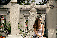 Turkish girl amongst Ottoman tombstones at the Suleymaniye Mosque in Istanbul, Turkey