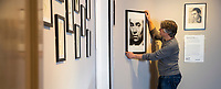 BNPS.co.uk (01202) 558833. <br /> Pic: CorinMesser/BNPS<br /> <br /> Pictured: Museum Director Adrian Green hangs a portrait of Richard Chopping in the exhibition. <br /> <br /> Original artwork from the acclaimed James Bond illustrator has gone on display at a new exhibition.<br /> <br /> Richard Chopping produced the drawings for nine of the 007 book covers from 1957 to 1966.<br /> <br /> Examples of his craft, including his striking skull design for Goldfinger, are being showcased at Salisbury Museum in Wiltshire.