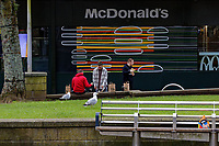 Pictured: Three people have a McDonalds meal near two seagulls. Friday 19 March 2021<br /> Re: City centre of Swansea, Wales, UK.
