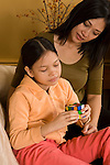 9 yera old girl playing with puzzle toy Rubik's Cube with mother vertical