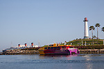 The Aqualink water taxi traveleing past the Rainbow Harbor Lighthouse to the Queen Mary in Long Beach, CA