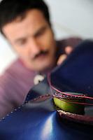 Claudio Sanò, artigiano del cuoio nel suo laboratorio mentre lavora un borsa a forma di pesce..Claudio Sanò, leather craftsman in his workshop, while he working a bag like a form of  big fish..
