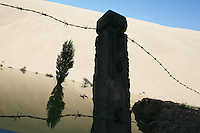 Sand dunes near the tourist attraction Ming Sha Shan. Desertification is the process by which fertile land becomes desert, typically as a result of drought, deforestation, or inappropriate agriculture. 41 % of China's landmass in classified as arid or desert. Inappropriate farming methods and over cultivation have contributed to the spreading of deserts in China in recent years. Dunhuang, Gansu Province. China