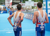 24 JUN 2012 - KITZBUEHEL, AUT - Alistair Brownlee (GBR) of Great Britain (right) winner of the elite men's 2012 World Triathlon Series round in Schwarzsee, Kitzbuehel, Austria and silver medalist Jonathan Brownlee (GBR) watch as Javier Gomez (ESP) of Spain as he runs to the finish line to claim third place (PHOTO (C) 2012 NIGEL FARROW)