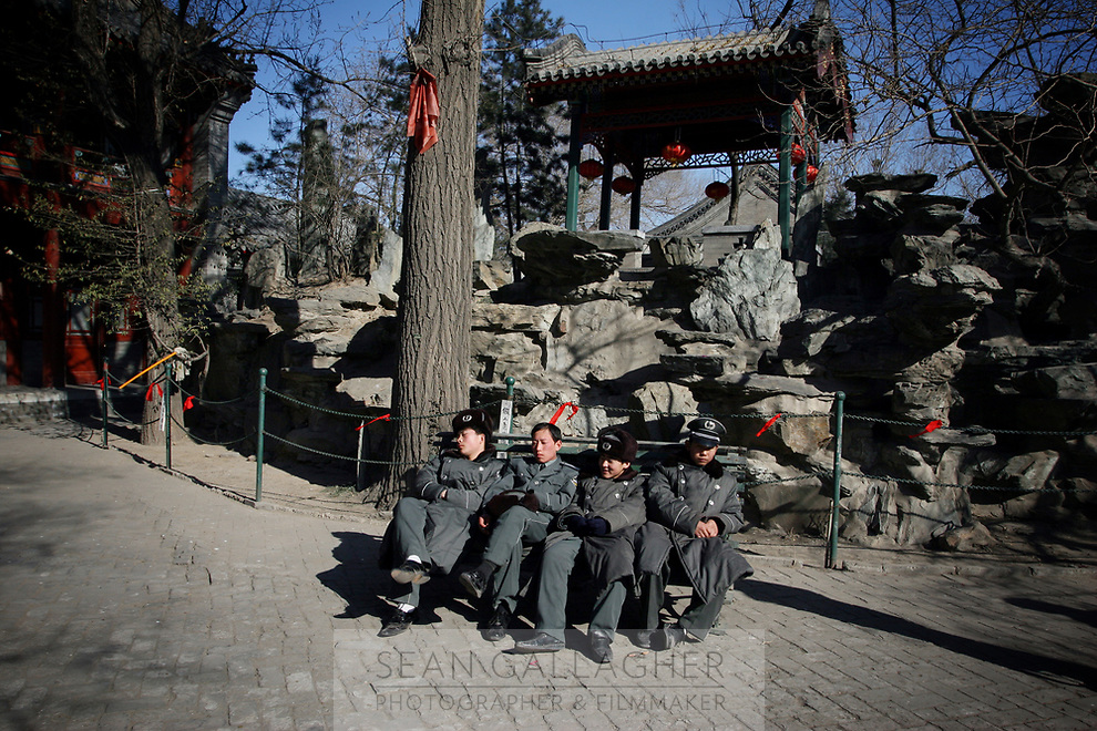 CHINA. Security guards taking a break during Chinese New Year in Baiyun Temple in Beijing.  Chinese New Year, or Spring Festival, is the most important festival and holiday in the Chinese calendar In mainland China, many people use this holiday to visit family and friends and also visit local temples to offer prayers to their ancestors. The roots of Chinese New Year lie in combined influences from Buddhism, Taoism, Confucianism, and folk religions.  2008