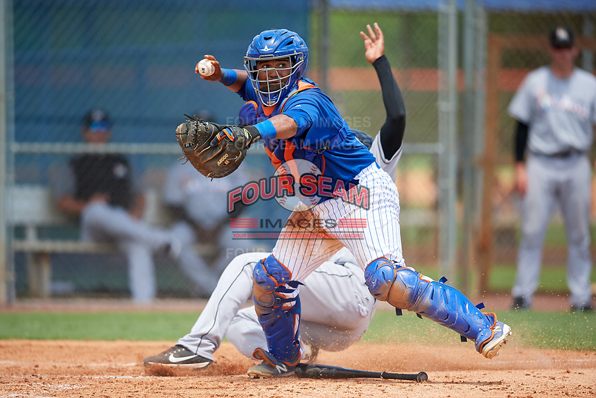 GCL Mets catcher Jose Mena (38) throws to first base as Christopher Rodriguez (7) slides home during a game against the GCL Marlins on August 3, 2018 at St. Lucie Sports Complex in Port St. Lucie, Florida.  GCL Mets defeated GCL Marlins 3-2.  (Mike Janes/Four Seam Images)