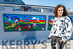 Lisa Harkin of Ballyheigue standing next to the mural she painted for Booleenshare NS in Ballyheigue