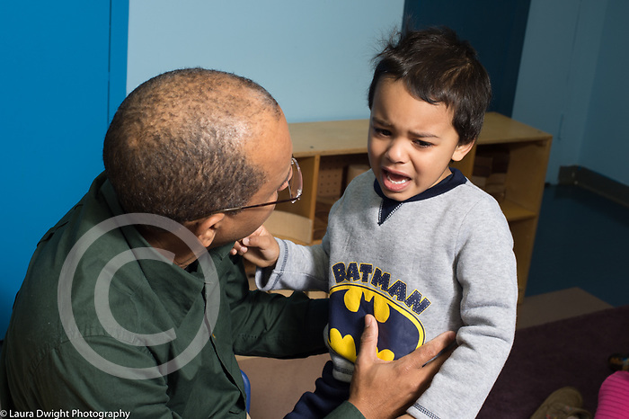 Education preschool 3-4 year olds male teacher talking to boy crying after conflict