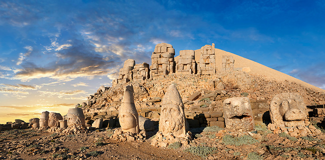 Statue heads at sunset, from right,  Eagle, Herekles, Apollo, Zeus, Commagene, Antiochus, & Eagle, with headless seated statues in front of the stone pyramid 62 BC Royal Tomb of King Antiochus I Theos of Commagene, east Terrace, Mount Nemrut or Nemrud Dagi summit, near Adıyaman, Turkey