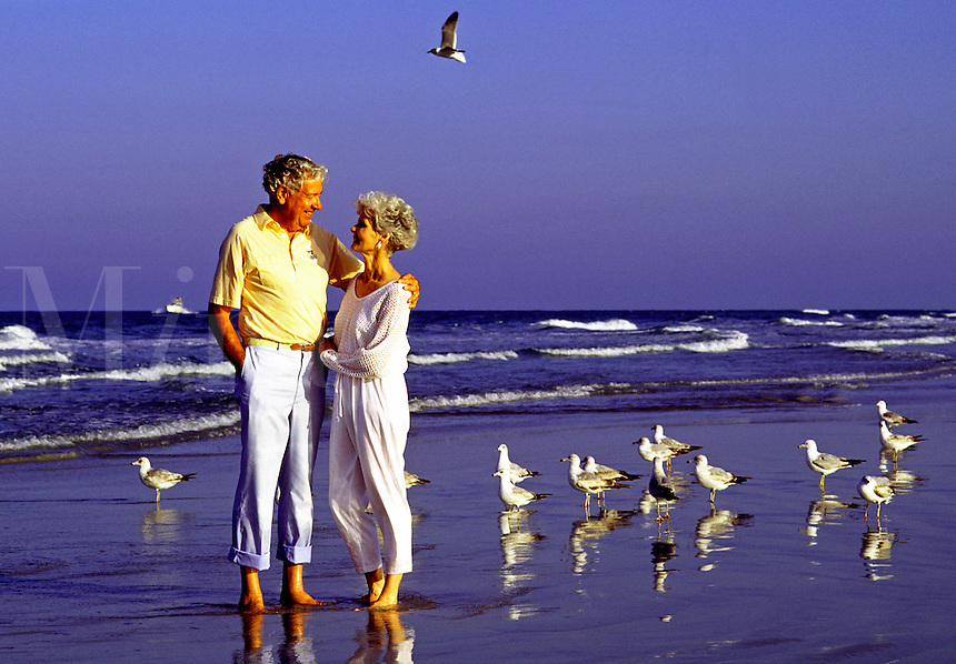 An affectionate senior couple embrace on the beach.