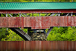 The red Taftsville covered bridge reflected in the Ottaquechee River in Hartland, VT, USA