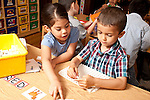 Education Preschool Headstart 4-5 year olds boy and girl doing letter game activity together