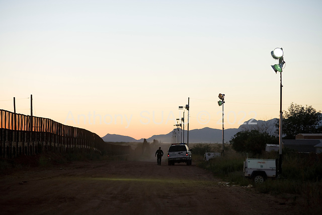 Naco, Arizona.USA.October 21, 2006...A member of the USA border patrol turns on the generators to light the border fence as night falls. The fence is to deter illegal immigration at this border crossing. Thousands of illegal immigrants cross this border every year,