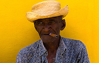 Local old man with cigar against bright yellow wall of building of the old colonial city of Trinidad in Cuba
