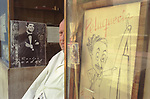 Carlos Gardel Buenos Aires photograph in a barber shops window. The barber is sitting down outside waiting for a customer. 2000s 2002 Argentina
