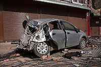 A dog sleeps in front of a destroyed car at Kathmandu, Nepal. May 03, 2015