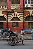 A rickshaw puller transports his rickshaw past a Kolkata Municipal Corporation building in the New Market area of Kolkata, India, on Friday, May 26, 2017. Photographer: Sanjit Das